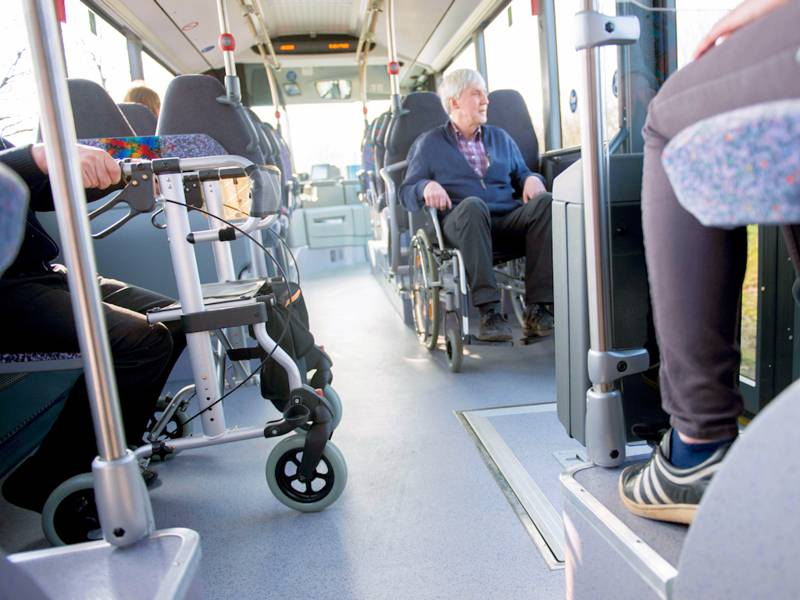 Mann in Rollstuhl und Rollator in Bus