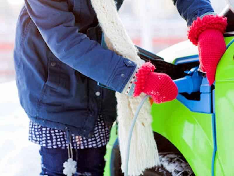 Mensch in Winterkleidung beim Laden eines E-Autos