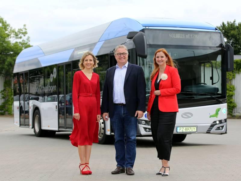 Zwei Frauen und ein Mann vor einem Bus