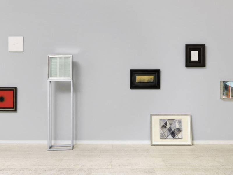 Gerahmte Bilder in verschiedenen Größen und unterschiedlichen Aufhängehöhen an einer Wand.