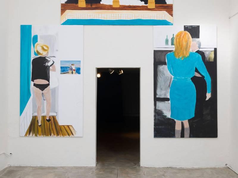 Wand mit Bildern und Durchgang in der Mitte.