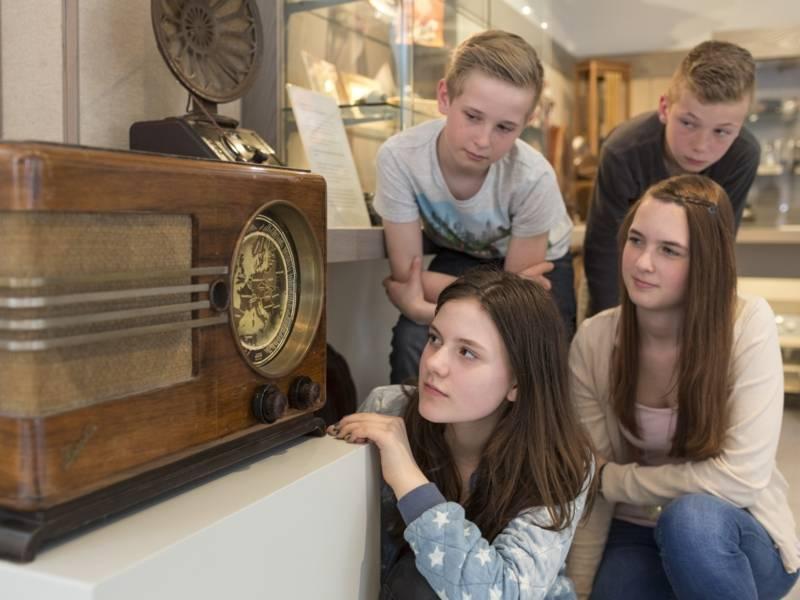 Zwei Mädchen und zwei Jungen vor einem alten Radioapparat