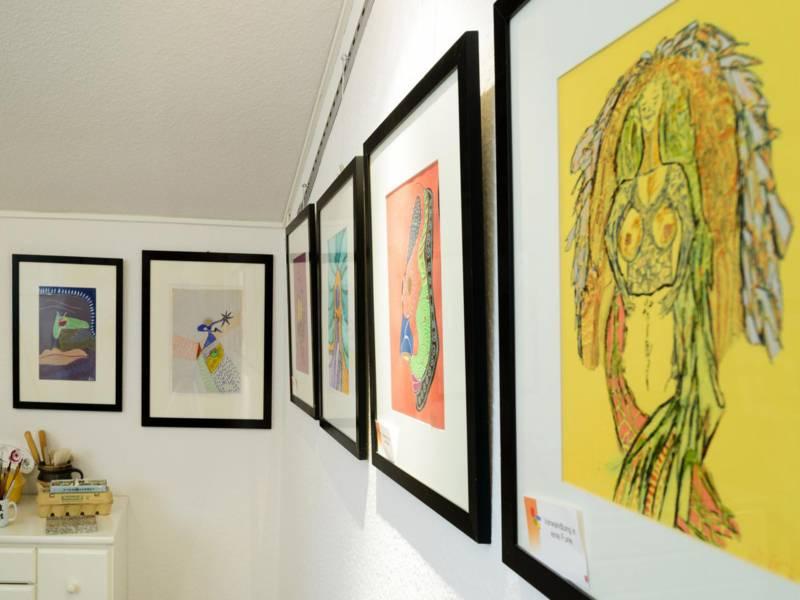 Bilder in Rahmen hängen an einer Wand.