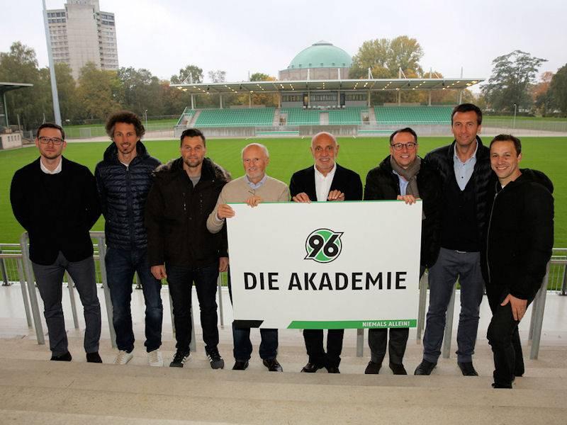 Gruppenbild mit acht Männern in einem Fußballstadion.