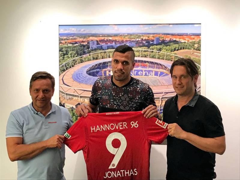 Drei Männer halten ein Trikot von Hannover 96 mit der Rückennummer 9 und der Aufschrift Jonathas.