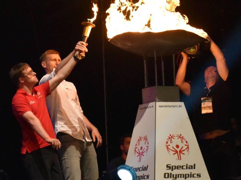 Foto: Jörg Trute und Per Mertesacker entzünden die olympische Flamme in der TUI-Arena.