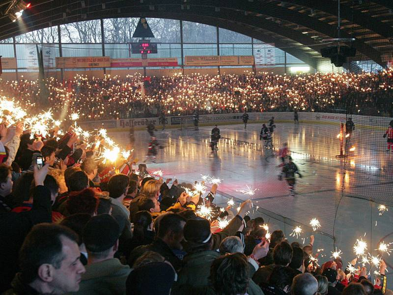 Menschen mit Wunderkerzen in den Händen in einem Eishockeystadion