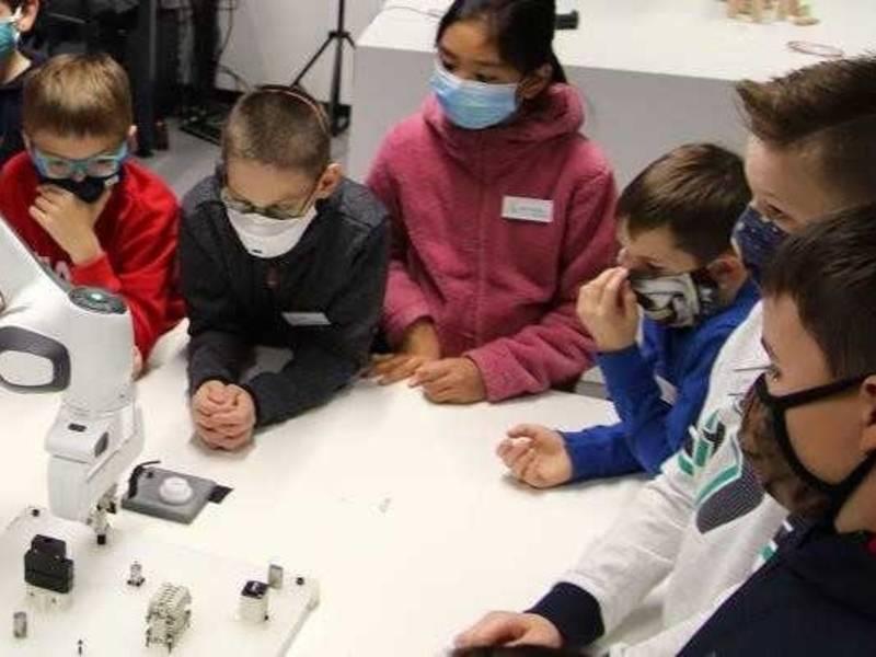 Sechs Kinder an einem Tisch mit einem Roboter