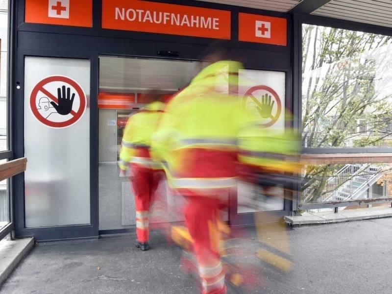 Zwei Sanitäter an einem Klinikeingang mit Schild Notaufnahme