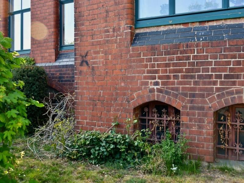Hausmauer mit schwarzem Kreuz