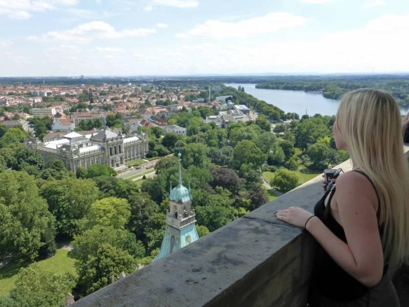 Eine Frau schaut sich die Landschaft von oben an.