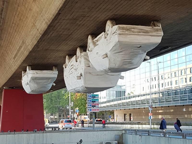 Drei kopfüber von einer Brücke hängende Autos