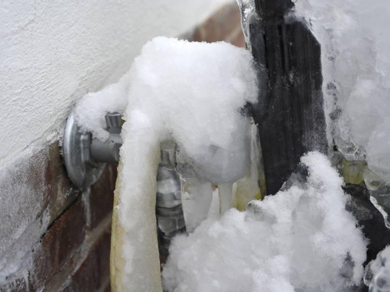 Vereister Wasseranschluss an einer Außenmauer.