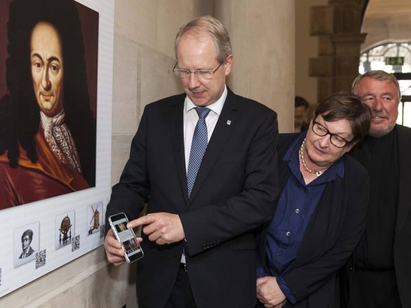 Mann hält ein Handy vor einer Bildtafel mit einem Strichcode, daneben stehen eine Frau und ein Mann.