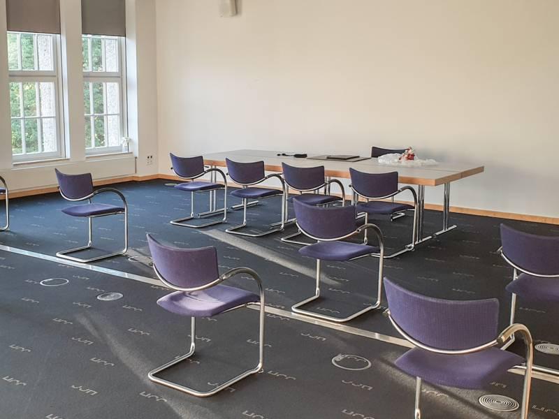 Ein Raum, in dem ein Tisch und mehrere Stühle stehen