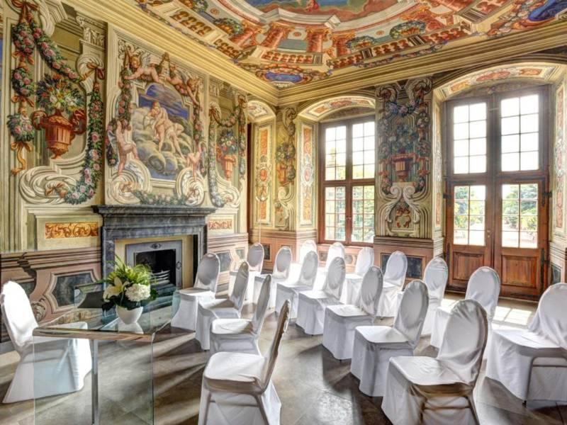 In einem mit zahlreichen Wandmalereien versehenen Raum mit hohen Fenstern sind vor einem Glastisch mit Blumenvase drei Stuhlreihen für eine Trauung aufgebaut.