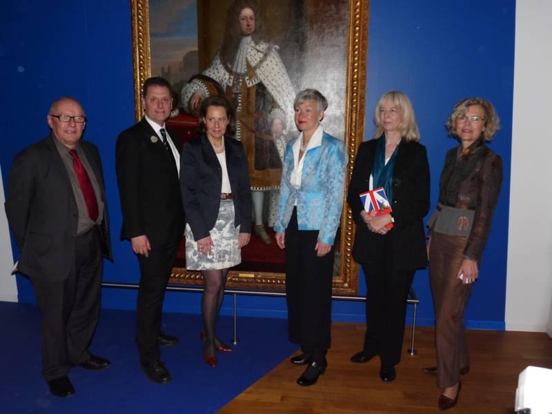 Vier Frauen und zwei Männer vor einm Gemälde König Georg des Ersten.
