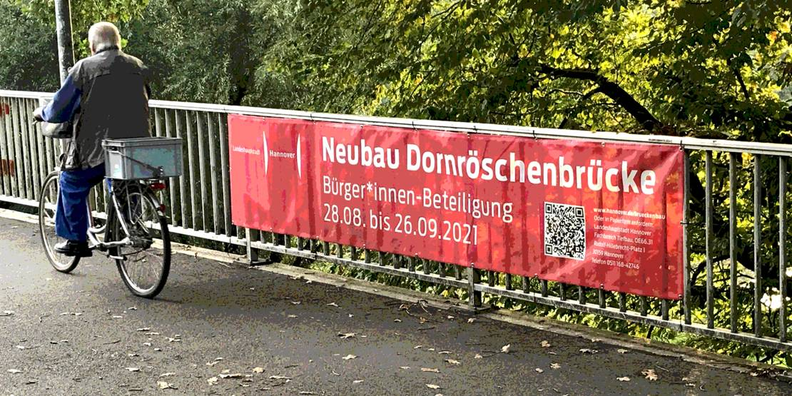 """Banner auf einer Brücke, auf dem """"Neubau Dornröschenbrücke"""" und ein QR-Code stehen. Eine Person auf einem Fahrrad fährt vorbei."""