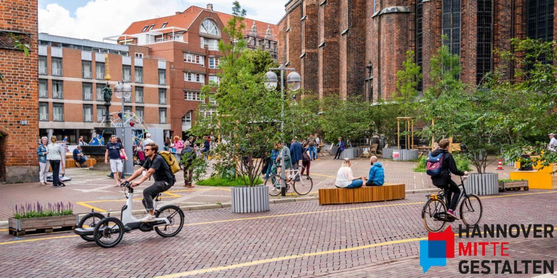 Radfahrende auf einer Straße. Im Hintergrund ein belebter Platz vor einer Kirche mit vielen Menschen. Am Rand ein Sitzbereich im Grünen.