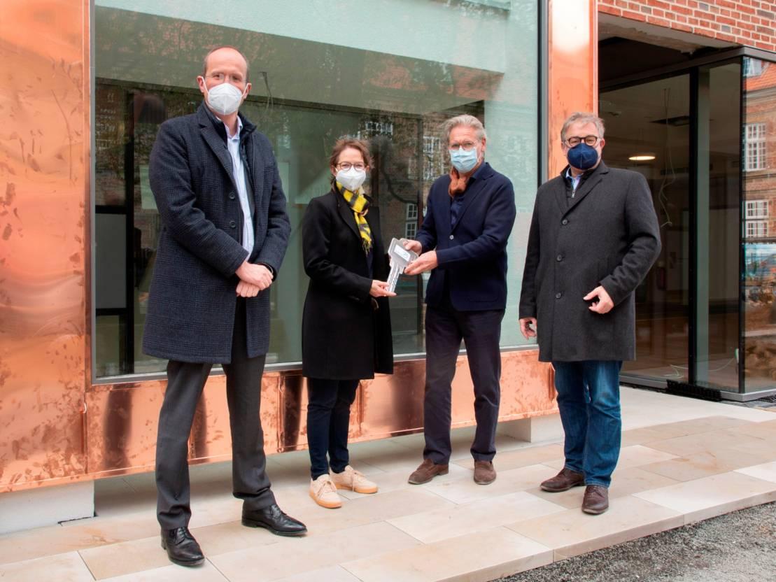 Drei Männer und eine Frau stehen vor der Tür eines neuen Gebäudes.