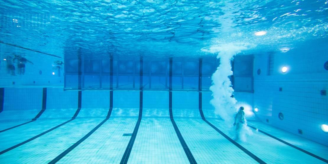 Unterwasseraufnahme einer Person, die ins Schwimmbecken gesprungen ist