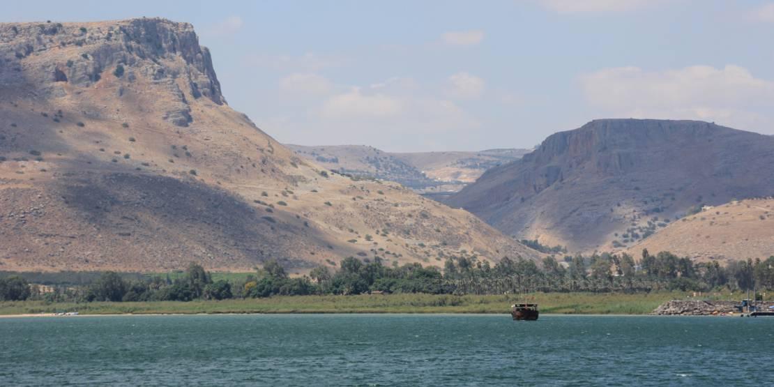 Im Vordergrund ein See mit einem Boot, im Hintergrund recht karge, aber imposante Berglandschaft