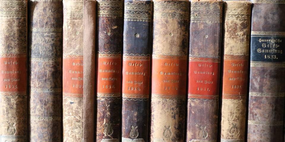 Neun sehr alte Bücher in einer Reihe aufgestellt.