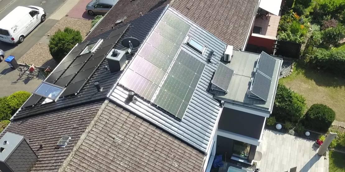 Luftaufnahme von mehreren Hausdächern, auf einem ist eine Photovoltaik-Anlage zu sehen