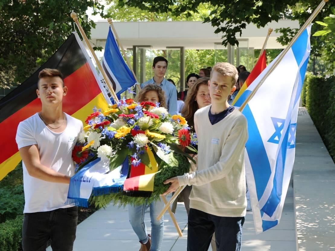 Zwei Jugendliche tragen einen mit Blumen geschmückten Kranz, dahinter gehen weitere Jungen und Mädchen mit Fahnen, zum Beispiel die des Staates Israel und der Bundesrepublik Deutschland.
