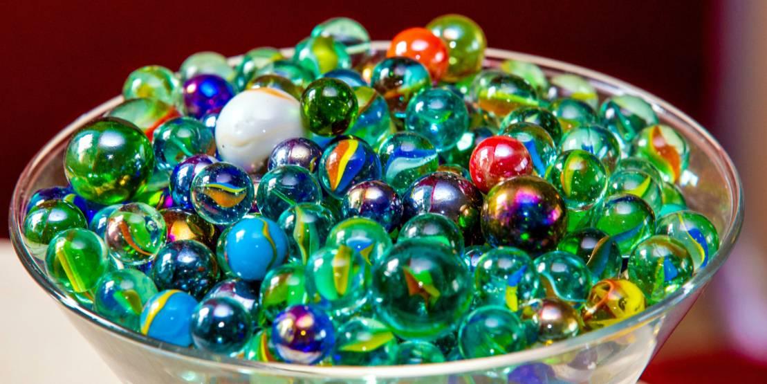 Viele verschiedene Murmeln liegen in einer Glasschale.