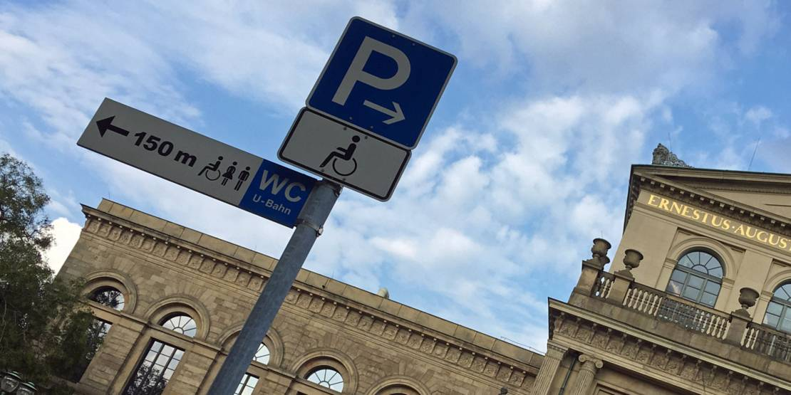 Schilder, die auf barrierefreie Parkplätze und Toiletten hinweisen vor einem alten Gebäude