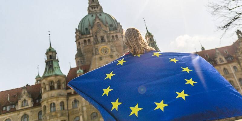 Eine Person mit Europaflagge vor dem Neuen Rathaus in Hannover.