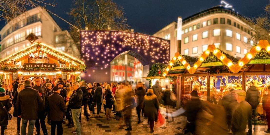 Menschen vor Weihnachtsmarktbuden und einem großen Eingangstor