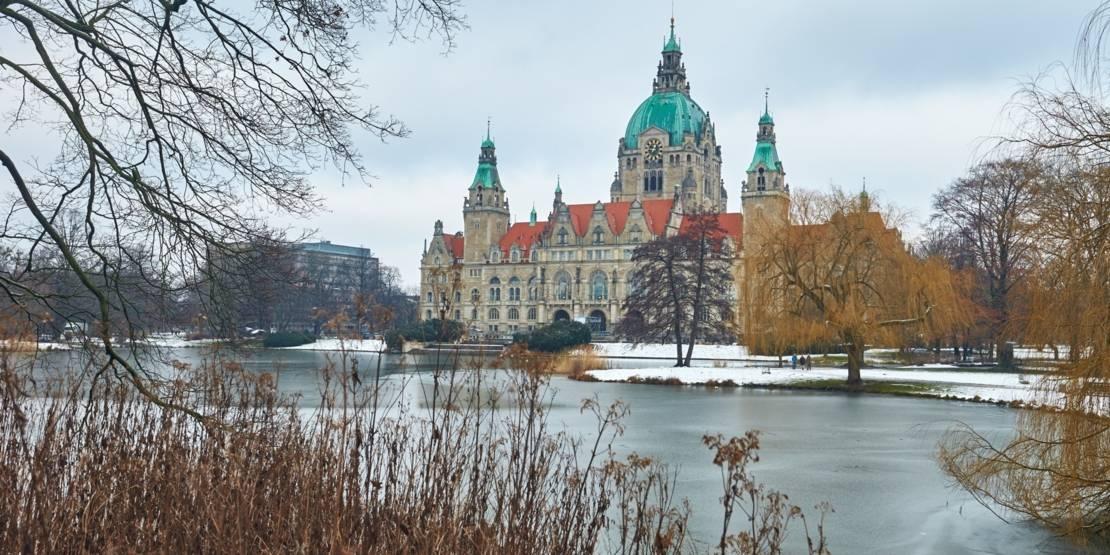 Historisches Gebäude hinter einem Teich in einem winterlichen Park.