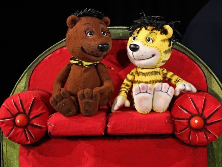 Bär- und Tigerpuppe auf einem Sofa.
