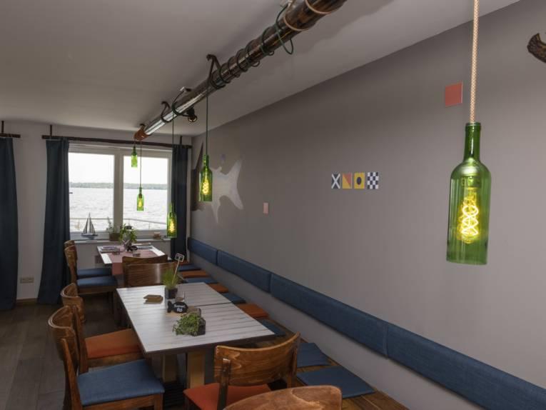 Der Innenraum des Restaurants mit Holzstühlen, blauen Sitzkissen, grünen Lampen