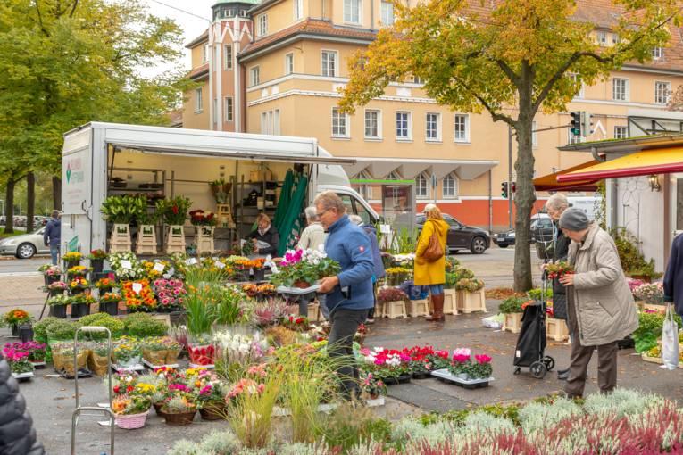 Blumen werden den Marktbesuchenden angeboten.