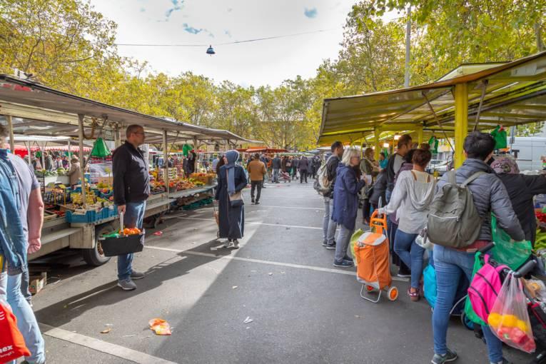 Kundschaft läuft zwischen Marktständen umher - Szenen vom Wochenmarkt Mitte an einem Samstag.