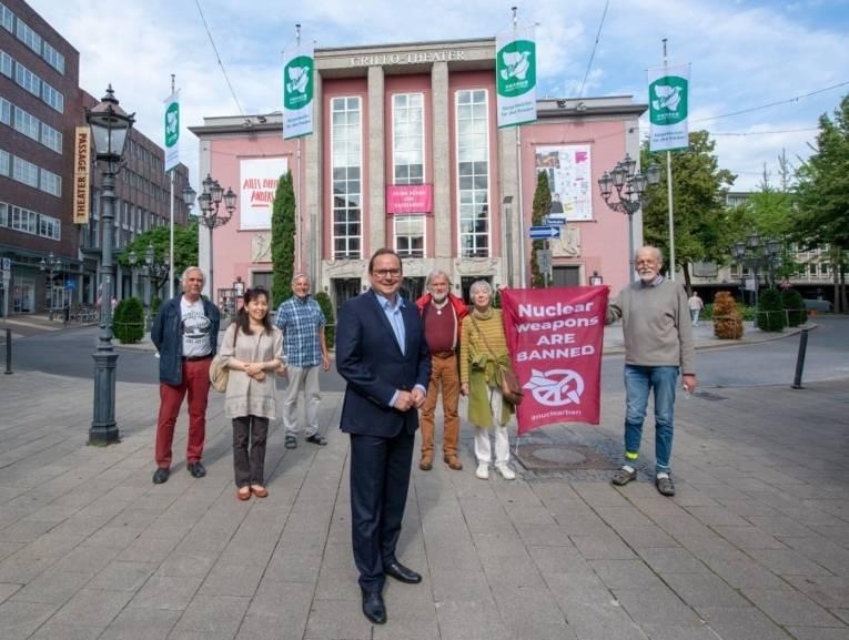 Der Essener Oberbürgermeister mit einiger Friedensgruppe vor dem beflaggten Rathaus