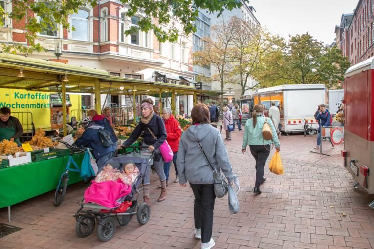 Menschen unterschiedlichen Alters (vom Kleinkind im Kinderwagen bis zur Seniorin) auf dem Wochenmarkt auf der Lister Meile.