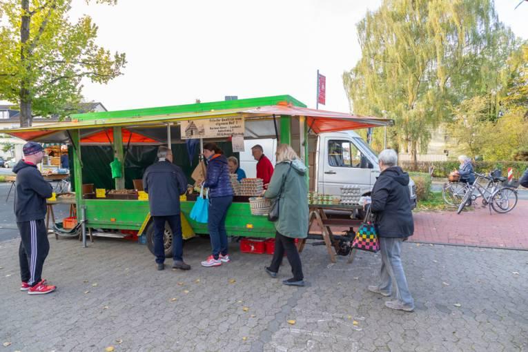 Menschen stehen an einem Marktwagen auf dem Wochenmarkt Misburg.