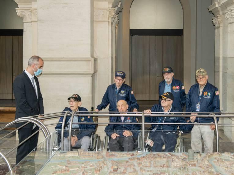 Oberbürgermeister Onay steht mit sechs US-Veteranen an einem Stadtmodell Hannovers.