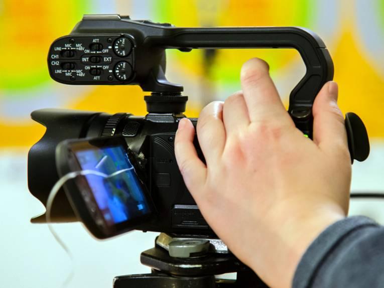 Eine Filmkamera filmt auf einem Stativ, die Hand einer Person ist an der Kamera.