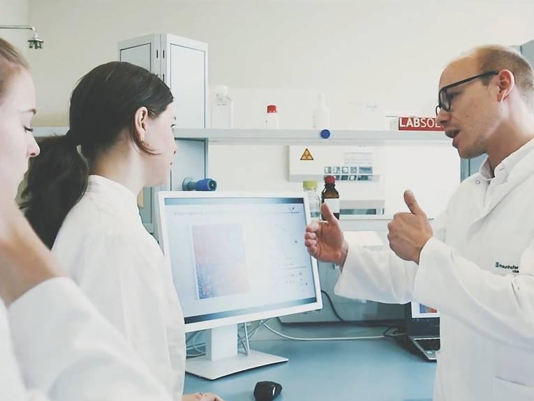 Ein Mann referiert für mehreren Personen vor einem Computerbildschirm. Alle Personen tragen Laborkleidung.