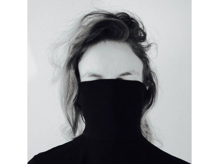 Eine Person in einem Pulli, der bis über die Augen über das Gesicht gezogen ist.
