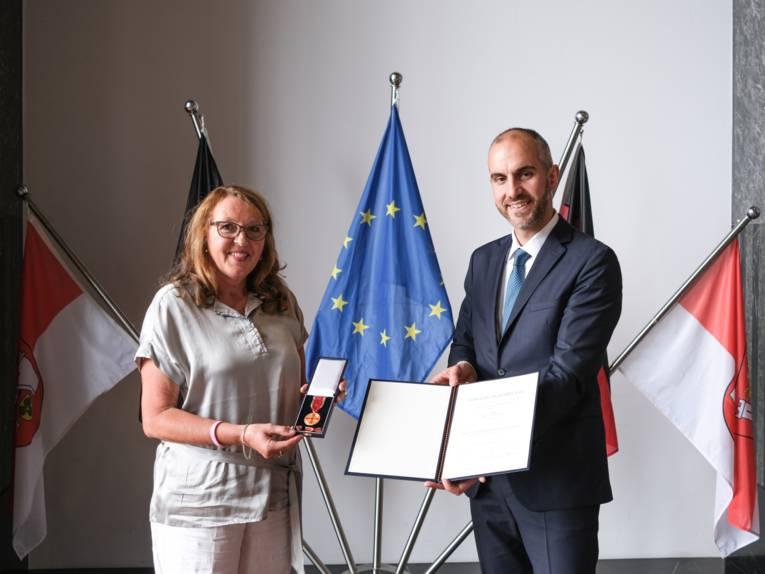 Links im Bild hält eine Frau die Verdienstmedaille in den Händen, rechts im Bild ein Mann die Verleihungsurkunde.