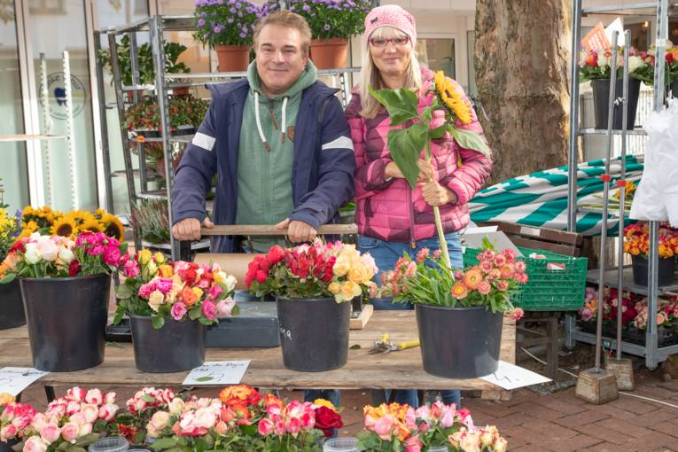Ein Mann und eine Frau an einem Blumenstand.