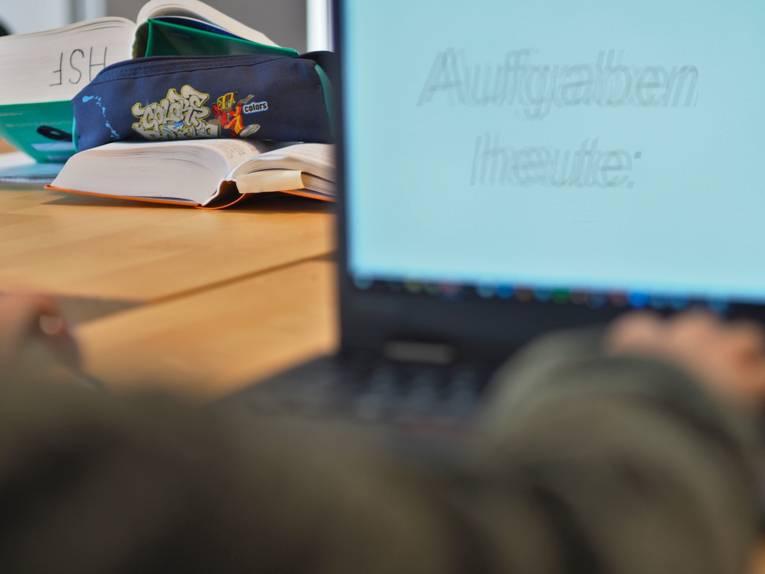 Zwei junge Menschen sitzen sich an einem Tisch gegenüber. Ein Kind arbeitet an einem Computer, der andere Jugendliche arbeitet mit gedruckten Büchern.