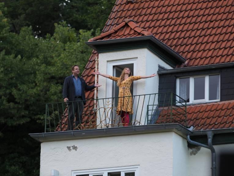 Ein Mann und eine Frau stehen auf einem Balkon. Sie trägt ein gelbes Blumenkleid und hält ihre Arme ausgestreckt in die Luft.