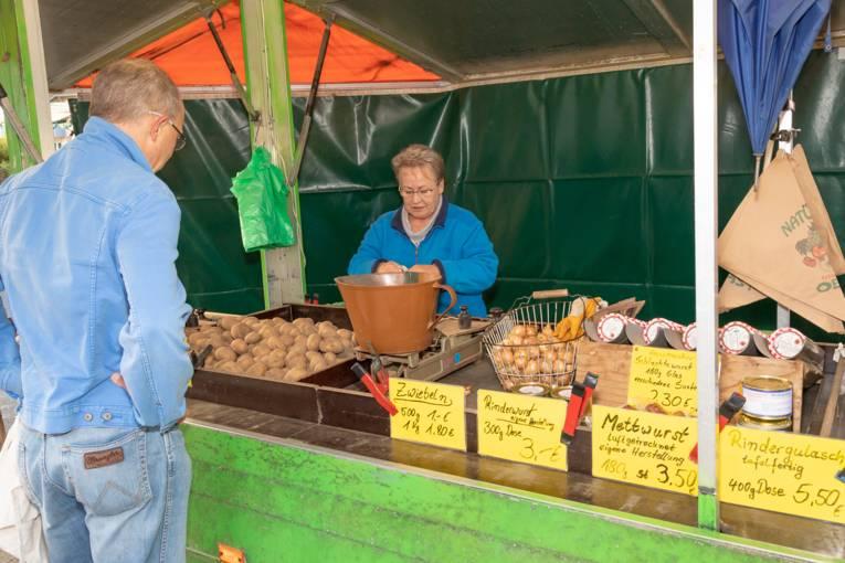 Ein Kunde kauft auf dem Wochenmarkt Misburg Kartoffeln und Wurstwaren.